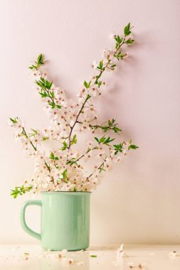 Mug with blossoming spring branches on table stock vector