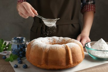 Woman sprinkling freshly baked cake