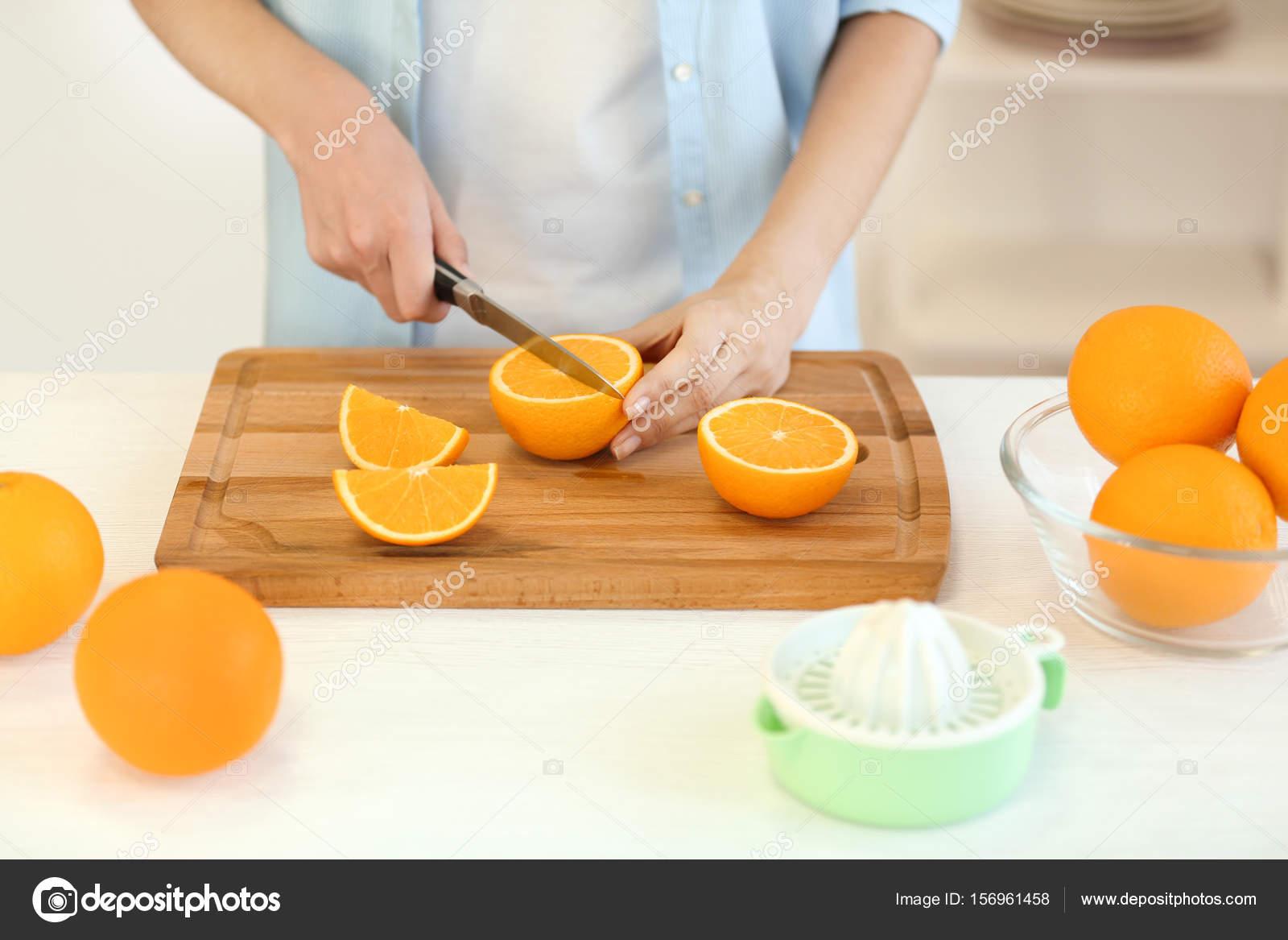 Weibliche Hände schneiden Orange auf Küche — Stockfoto © belchonock ...