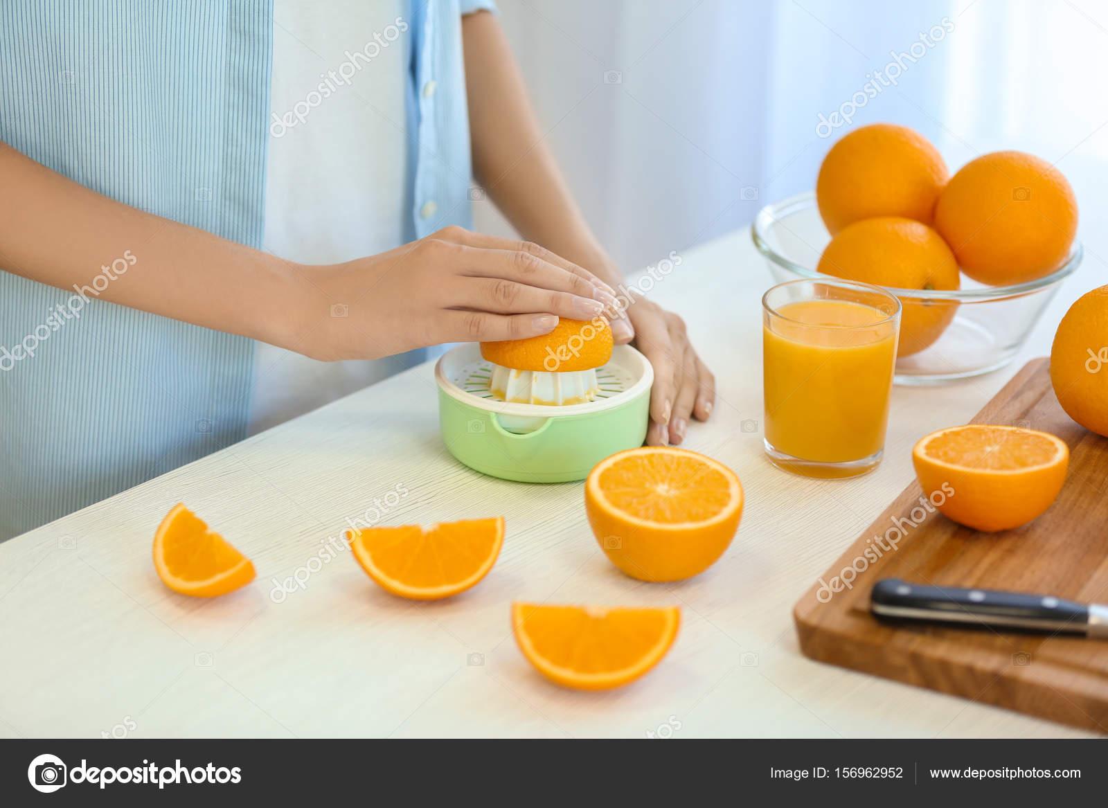 Weibliche Hände machen Orangensaft — Stockfoto © belchonock #156962952
