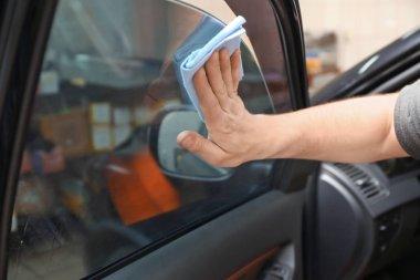 Worker polishing car window