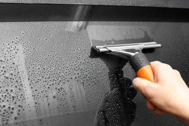 Worker washing car window
