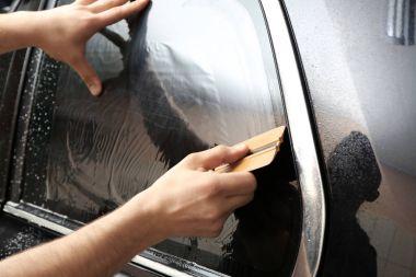 Worker installing foil on car window