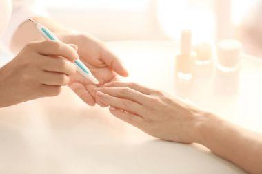 Woman making manicure in salon