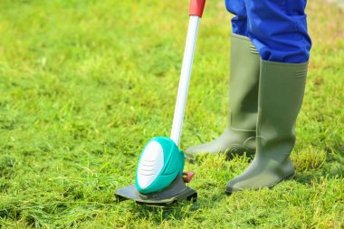 worker mowing lawn with grass trimmer