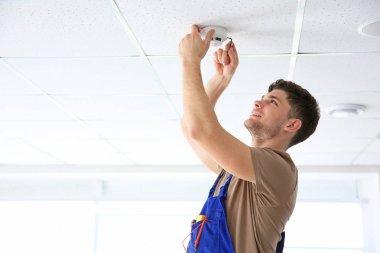 electrician installing smoke detector