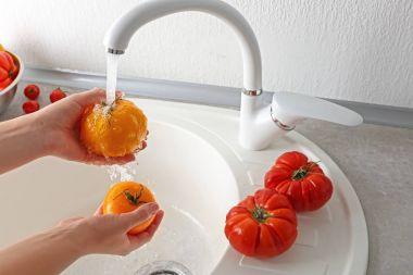 Female hands washing tomatoes