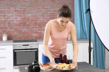 Young woman exposing food to take pictures in photo studio