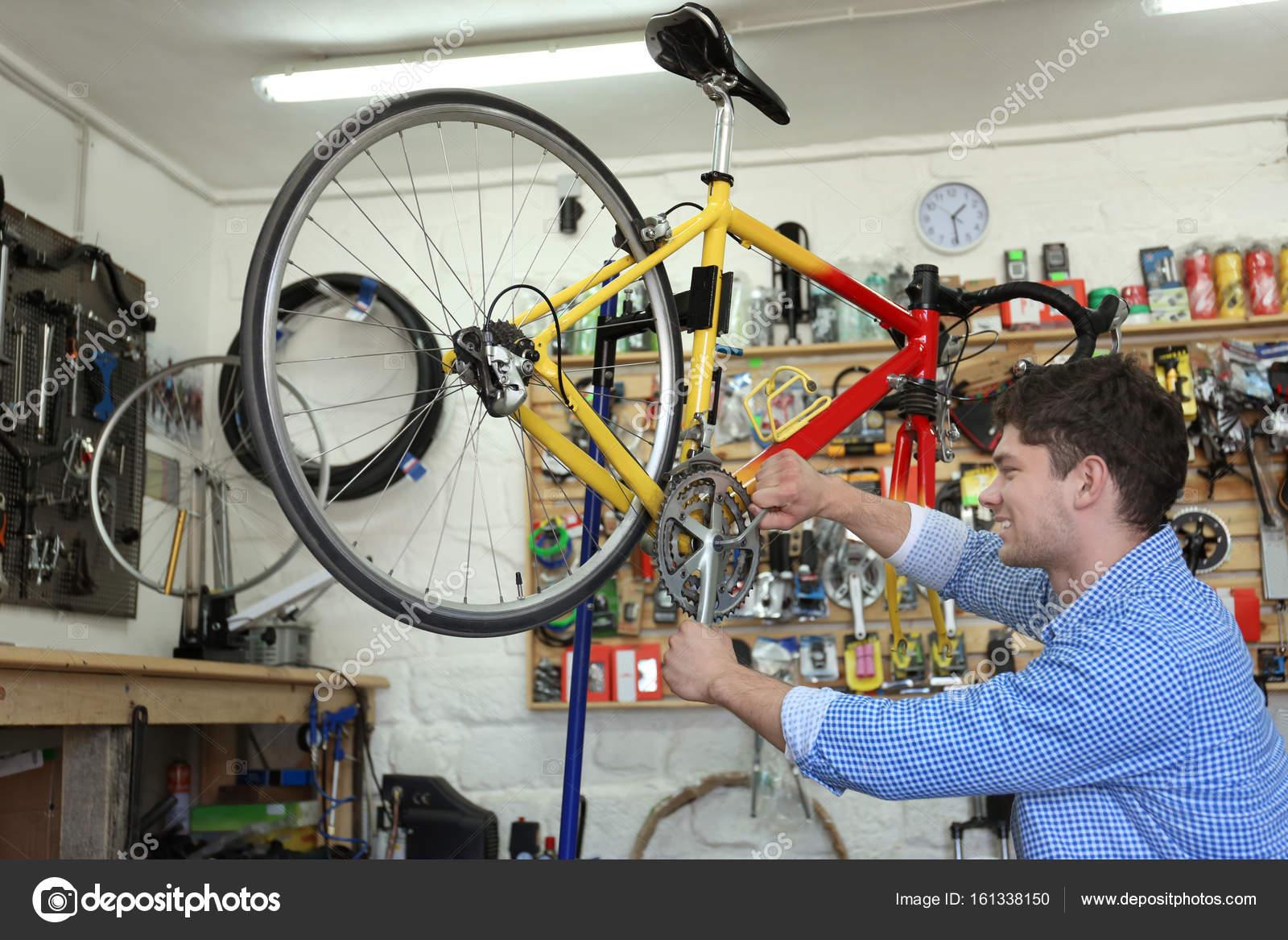 Man working in bicycle repair shop — Stock Photo