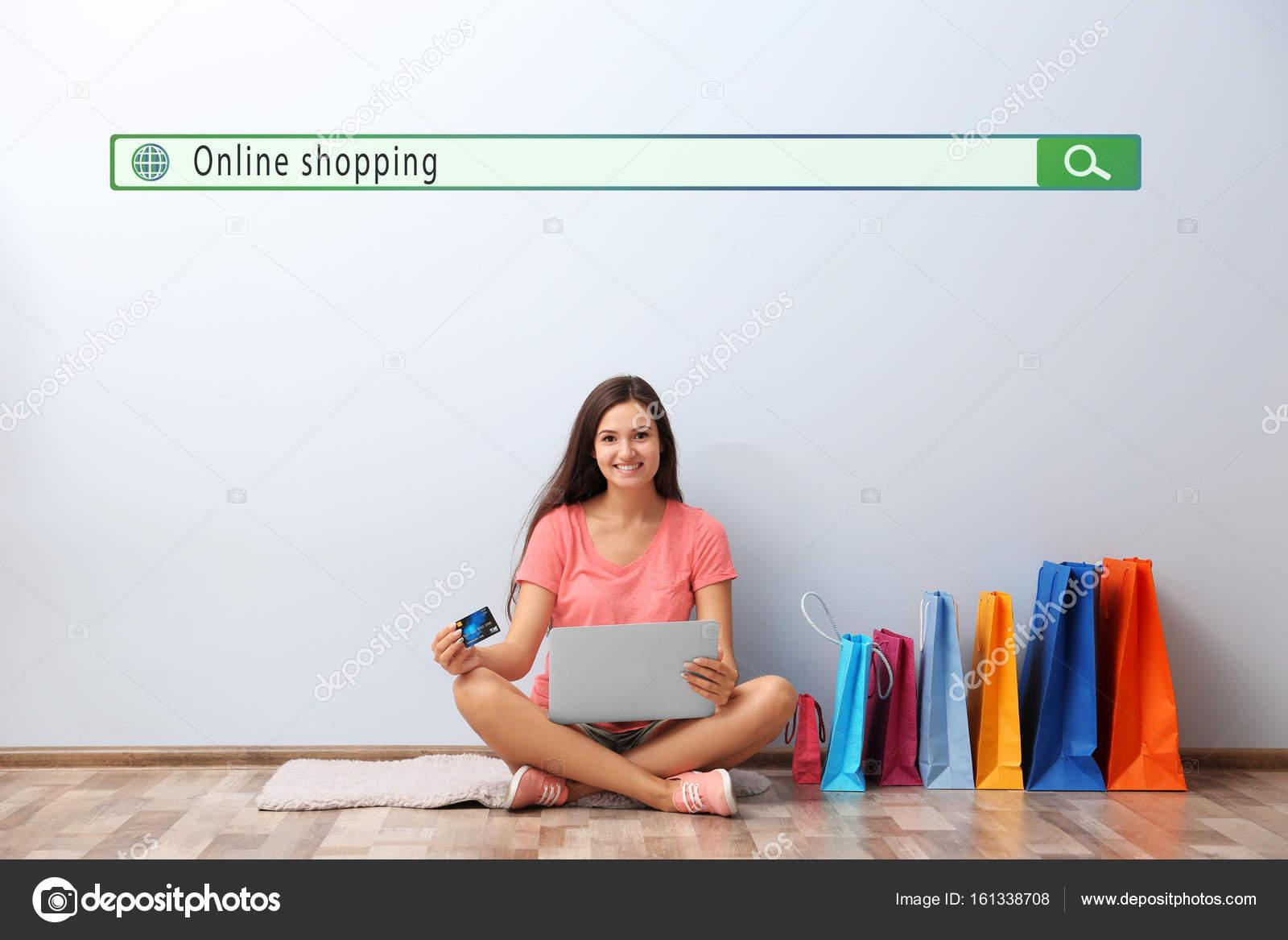 277e498ded3e1a Internet-shopping-Konzept. Junge Frau mit Kreditkarte und Laptop am Boden  zu Hause
