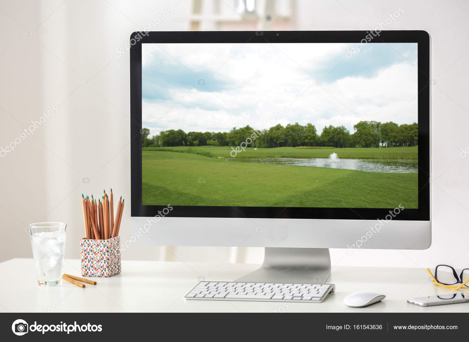 Workplace with computer monitor and wallpaper of landscape on screen — Stock Photo