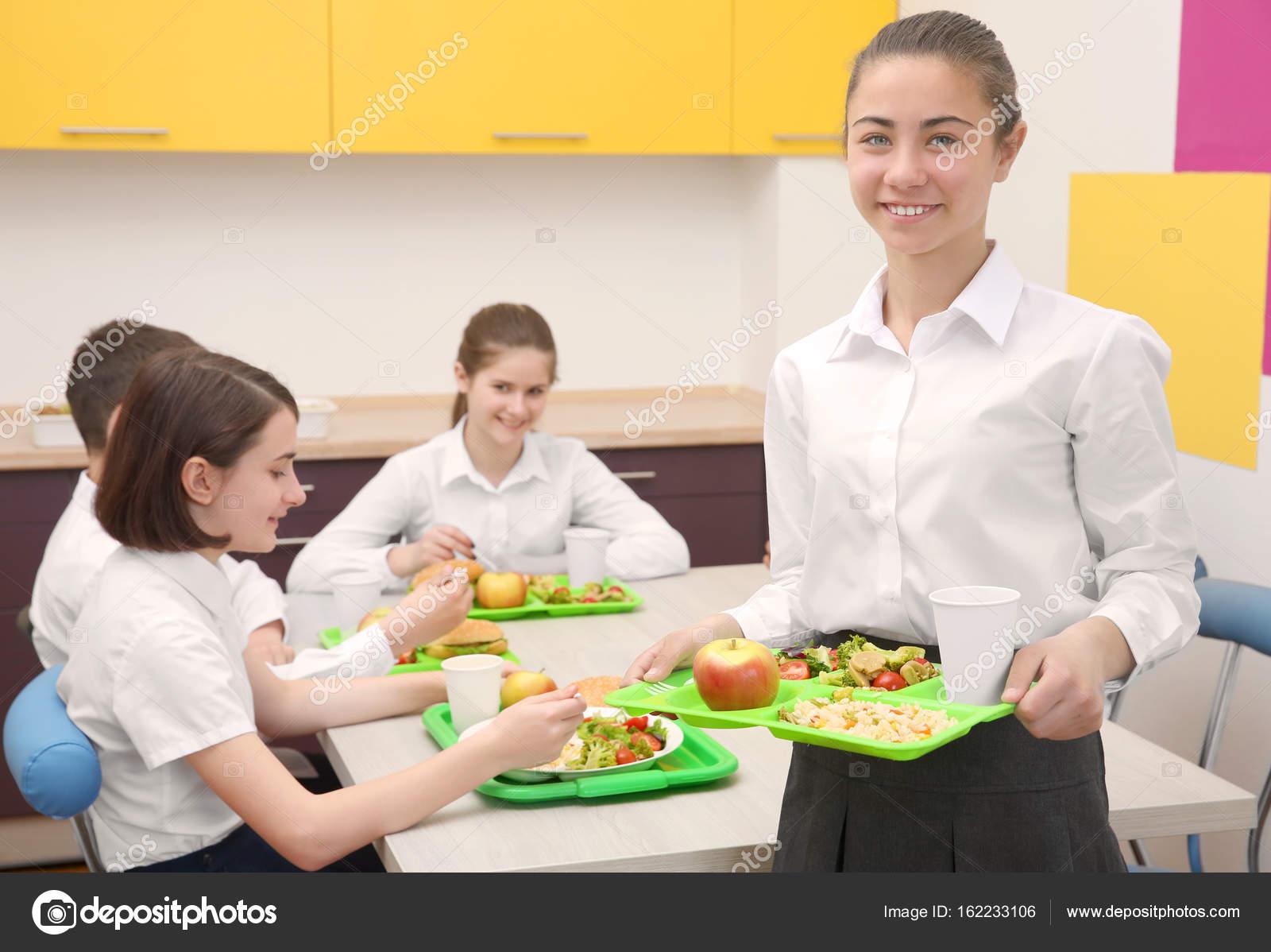 Linda chica sosteniendo la bandeja con deliciosa comida en comedor ...