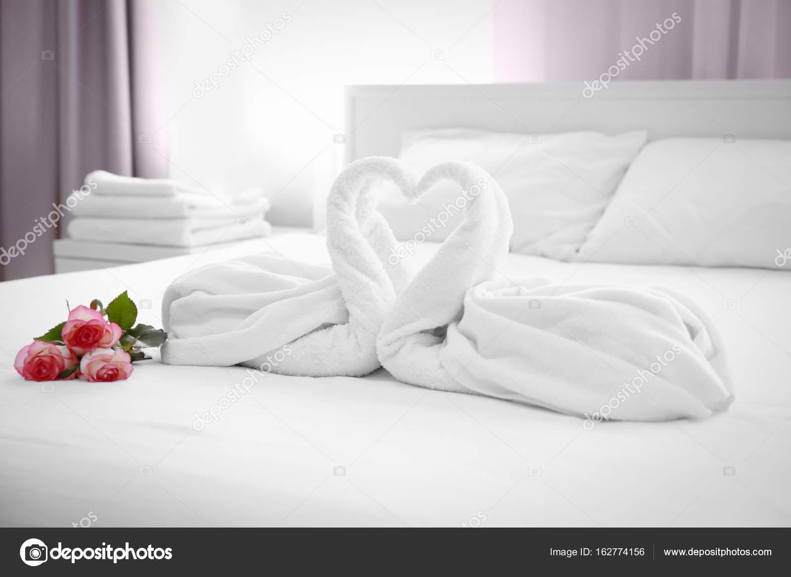 Due asciugamani cigni e bouquet di rose sul letto nella camera d 39 albergo foto stock - Foto di letto ...