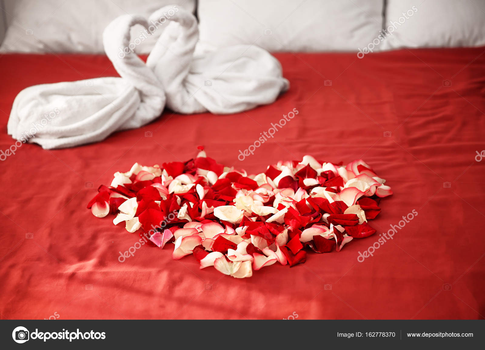 Due asciugamani cigni e petali di rosa sul letto nella - Foto di innamorati a letto ...