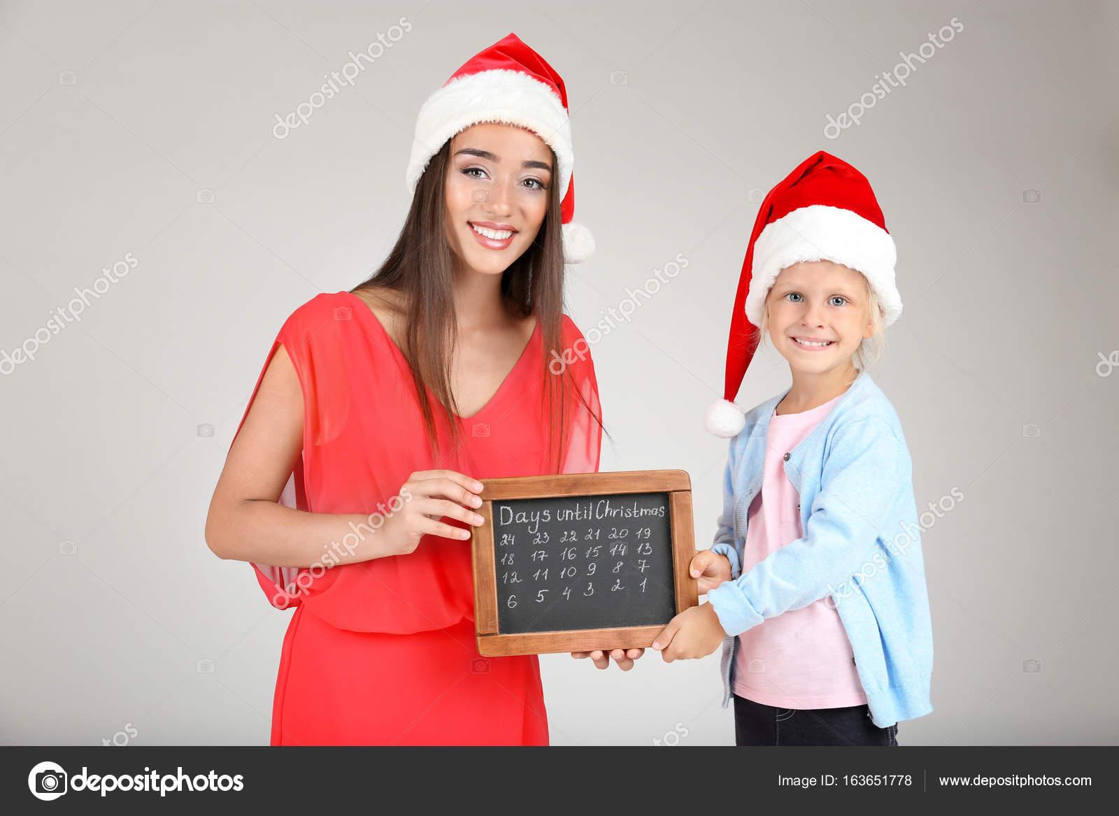 Junge Frau und niedliche kleine Mädchen in Santa Hüte mit Tafel ...