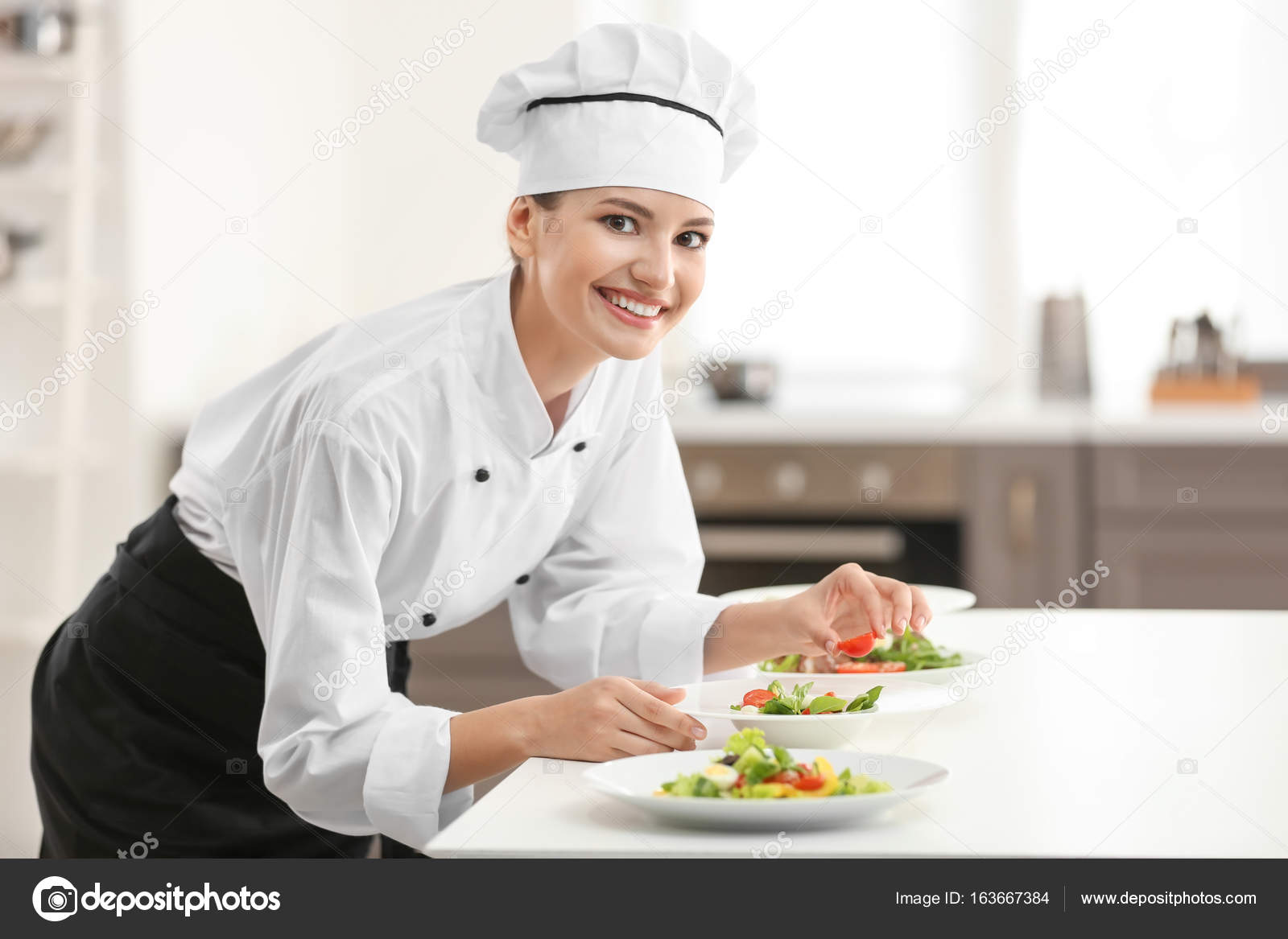Young female chef cooking in kitchen — Stock Photo © belchonock ...