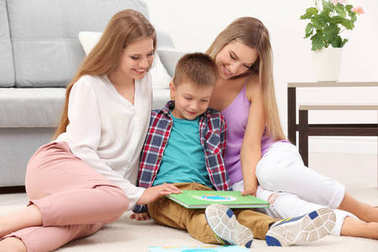 Lesbian couple reading with son
