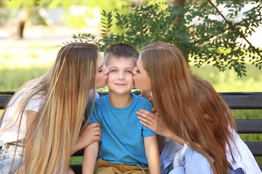 Happy lesbian mothers kissing foster son in park. Adoption concept