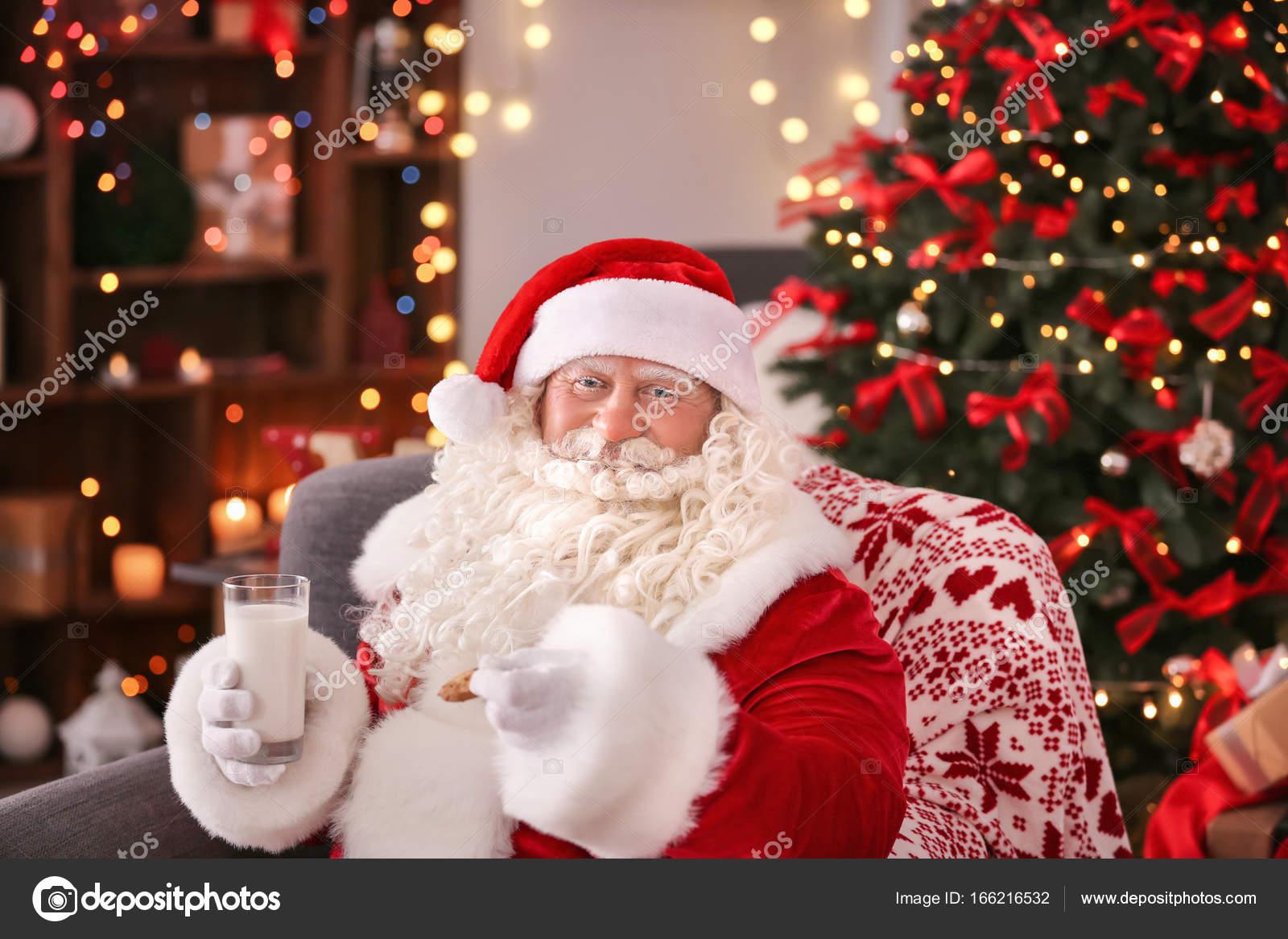 Auténtico Papa Noel con galletas y vaso de leche sentado en el sillón en la  sala decorada para la Navidad — Foto de belchonock 953e85f3028