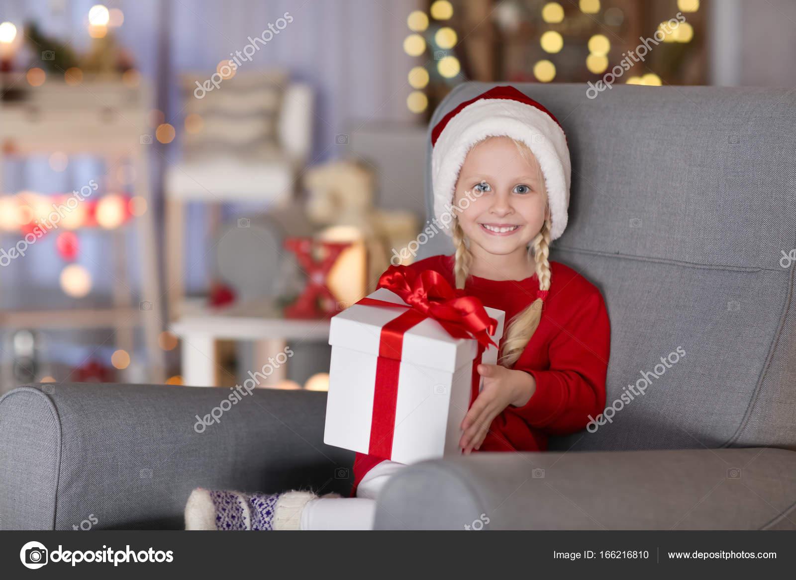 Niedliche Kleine Mädchen Mit Weihnachts Geschenk Box Sitzen Sessel ...