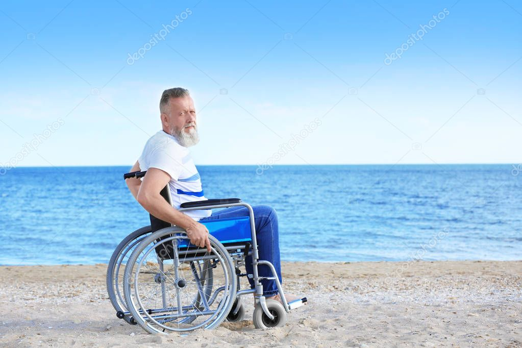 Elderly man in wheelchair on sea coast