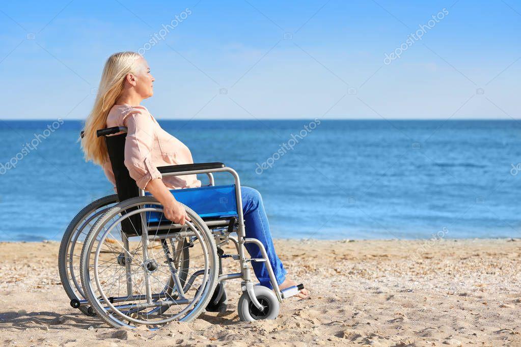 Elderly woman in wheelchair on sea coast