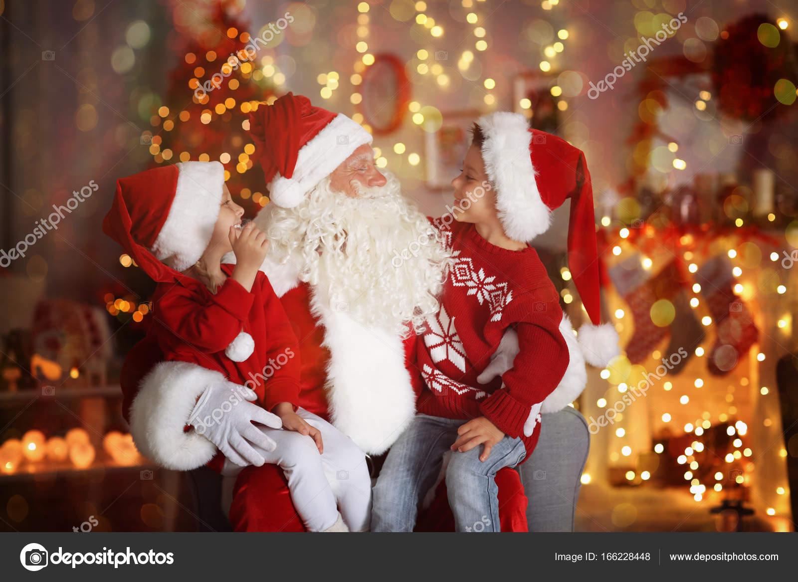 Schattige kleine jongen en meisje met de kerstman op kamer