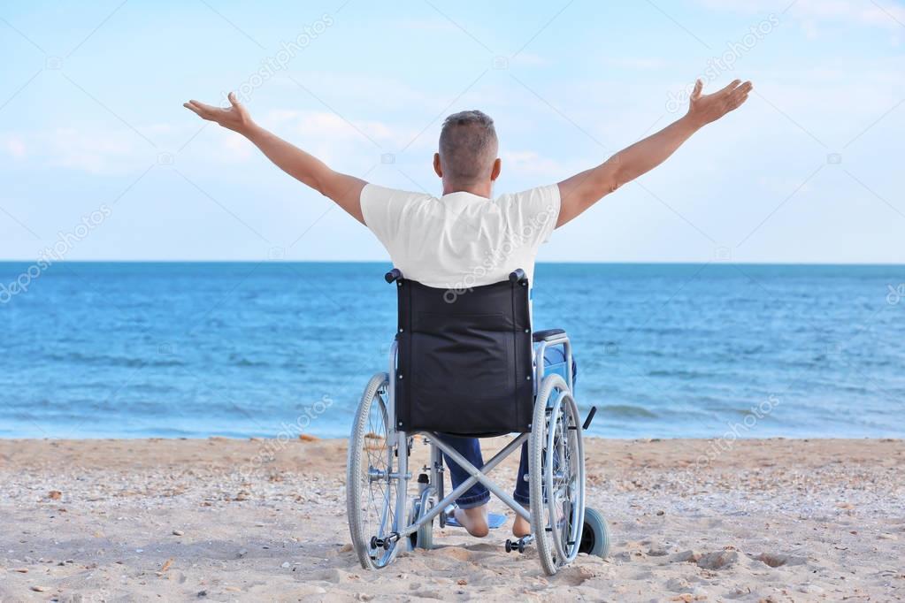 Elderly man in wheelchair on sea coast