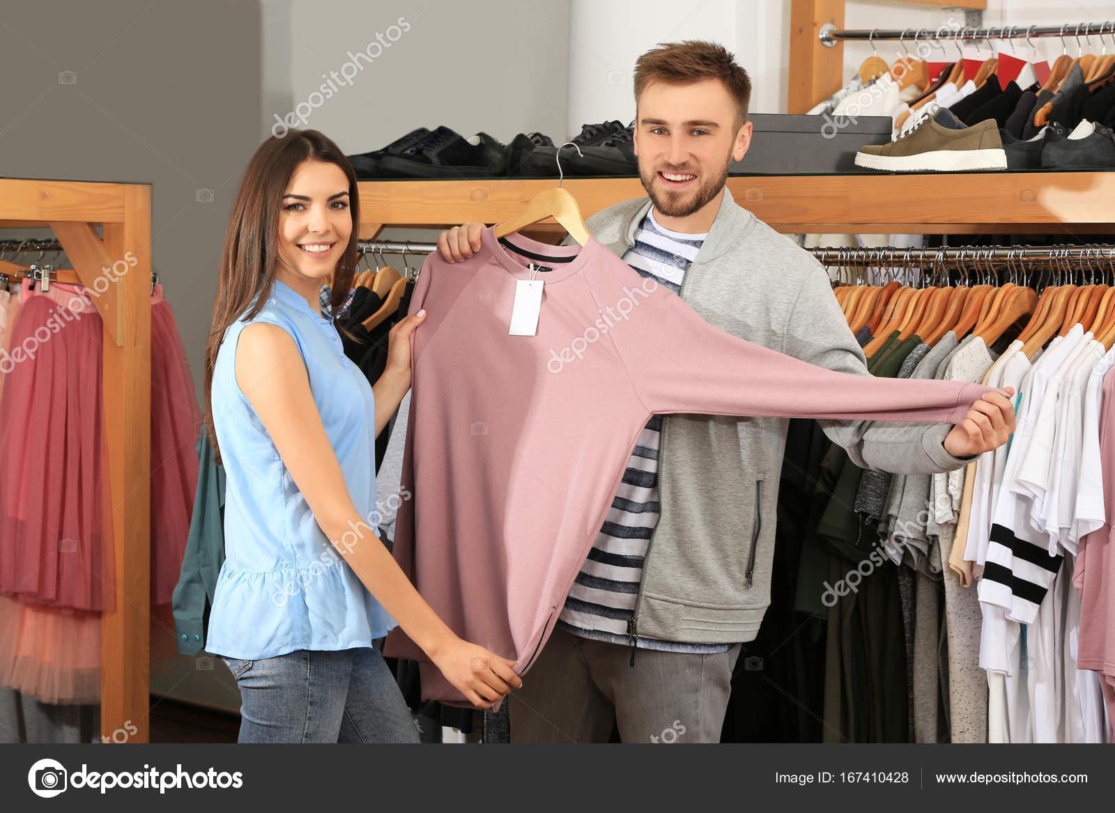 Joven pareja eligiendo ropa en centro comercial — Fotos de Stock ...