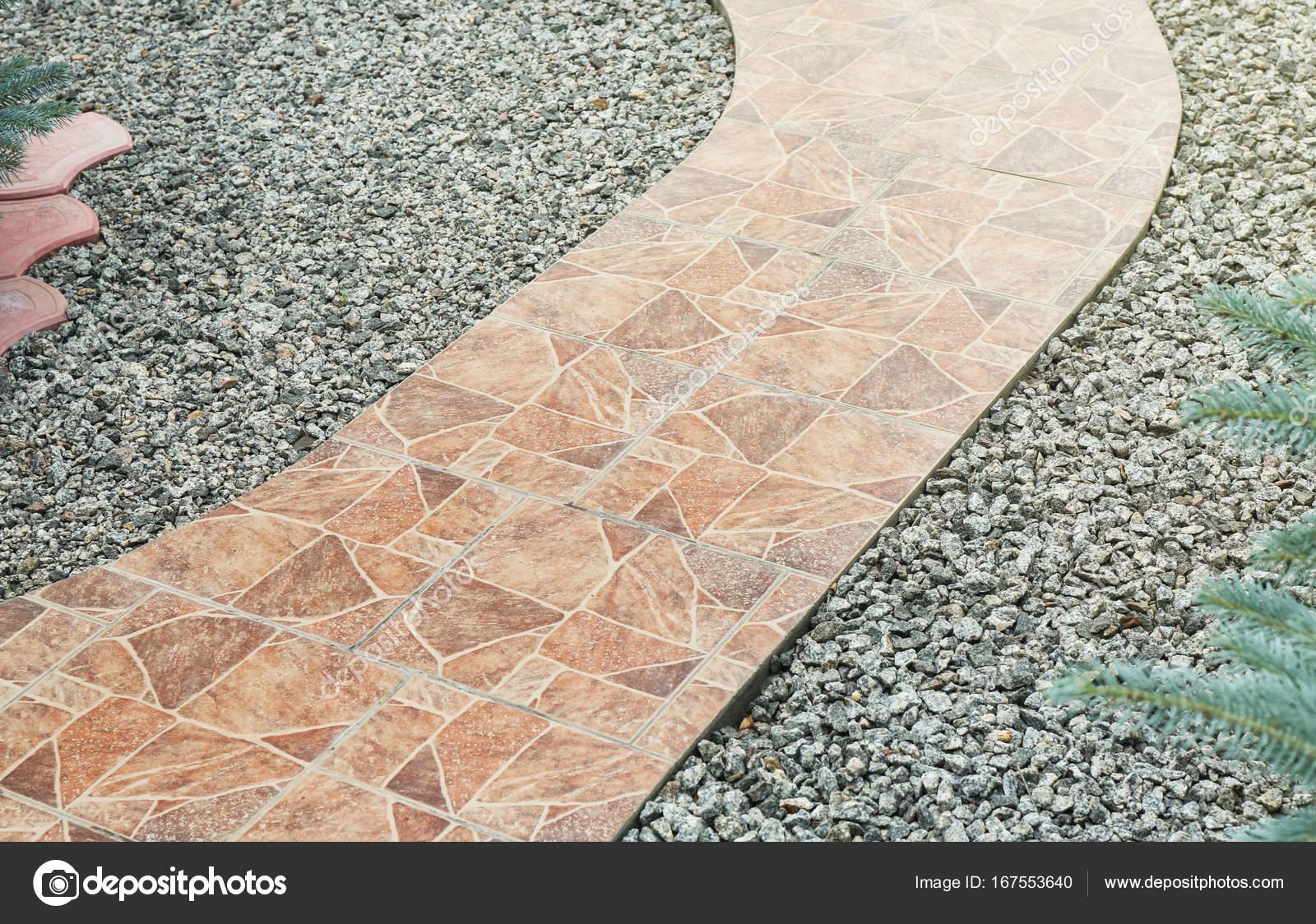 Via effettuata in piastrelle di ceramica con pietrisco in giardino