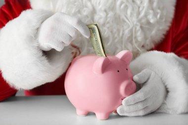 Santa Claus putting money into piggy bank at table