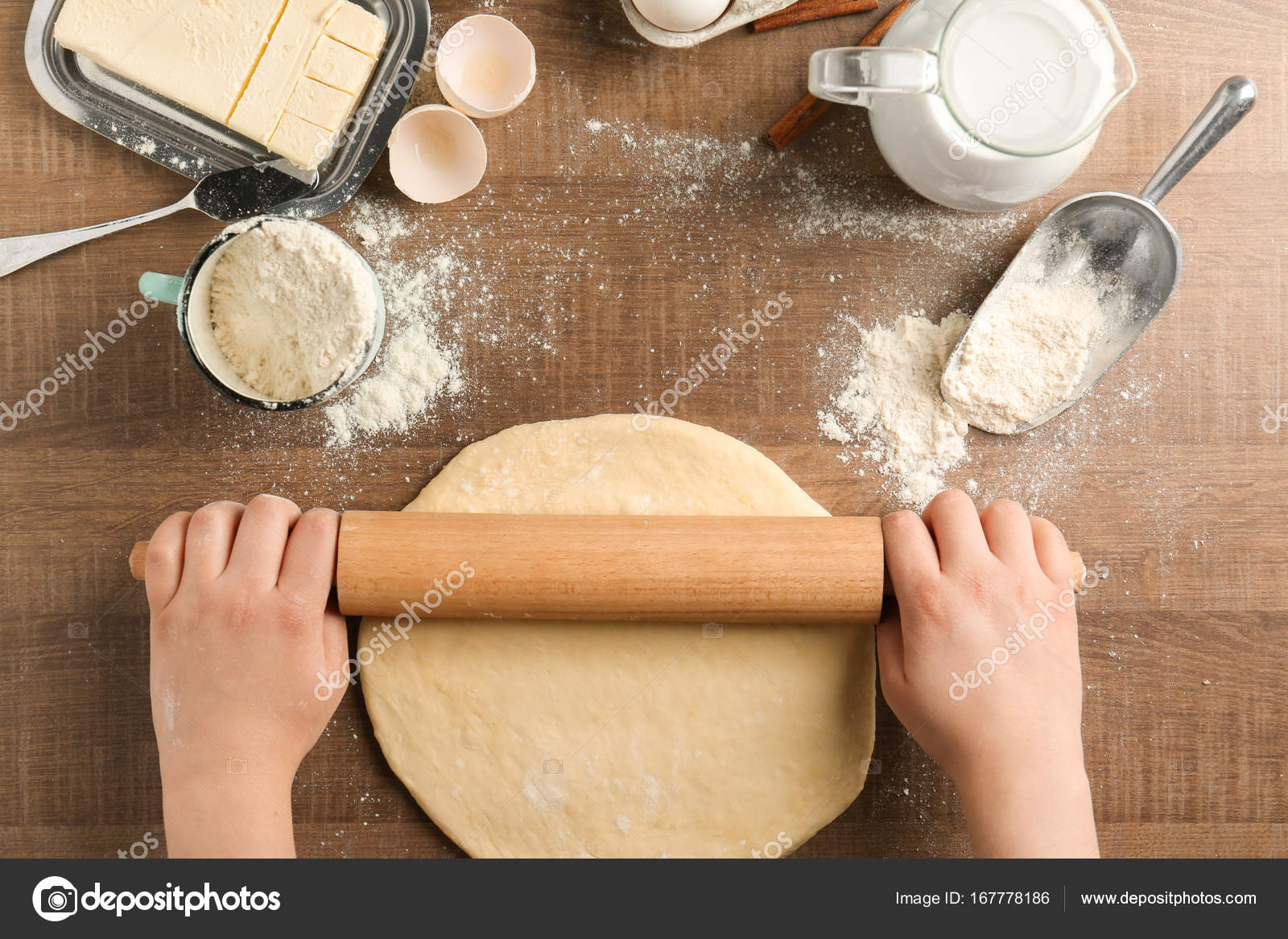 Woman rolling dough on kitchen table. Cooking classes concept ...