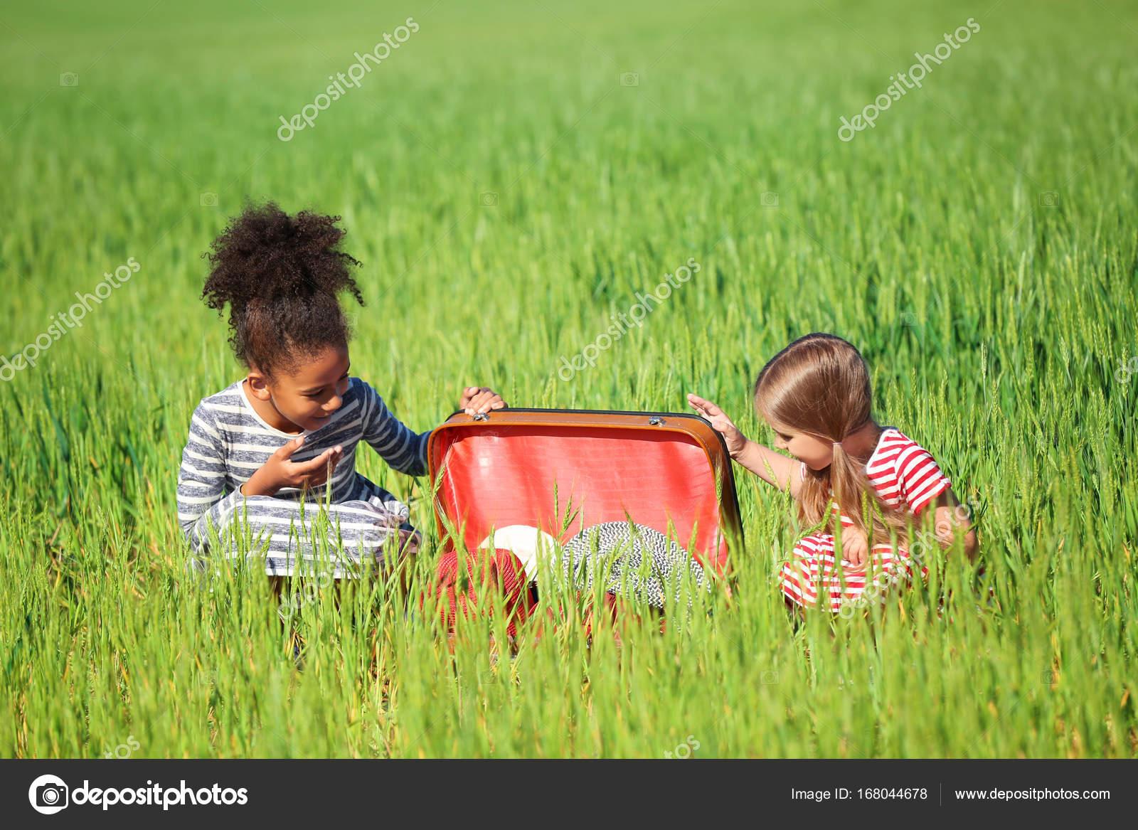 Glückliche Kleine Mädchen Mit Koffer Im Grünen Bereich Stockfoto