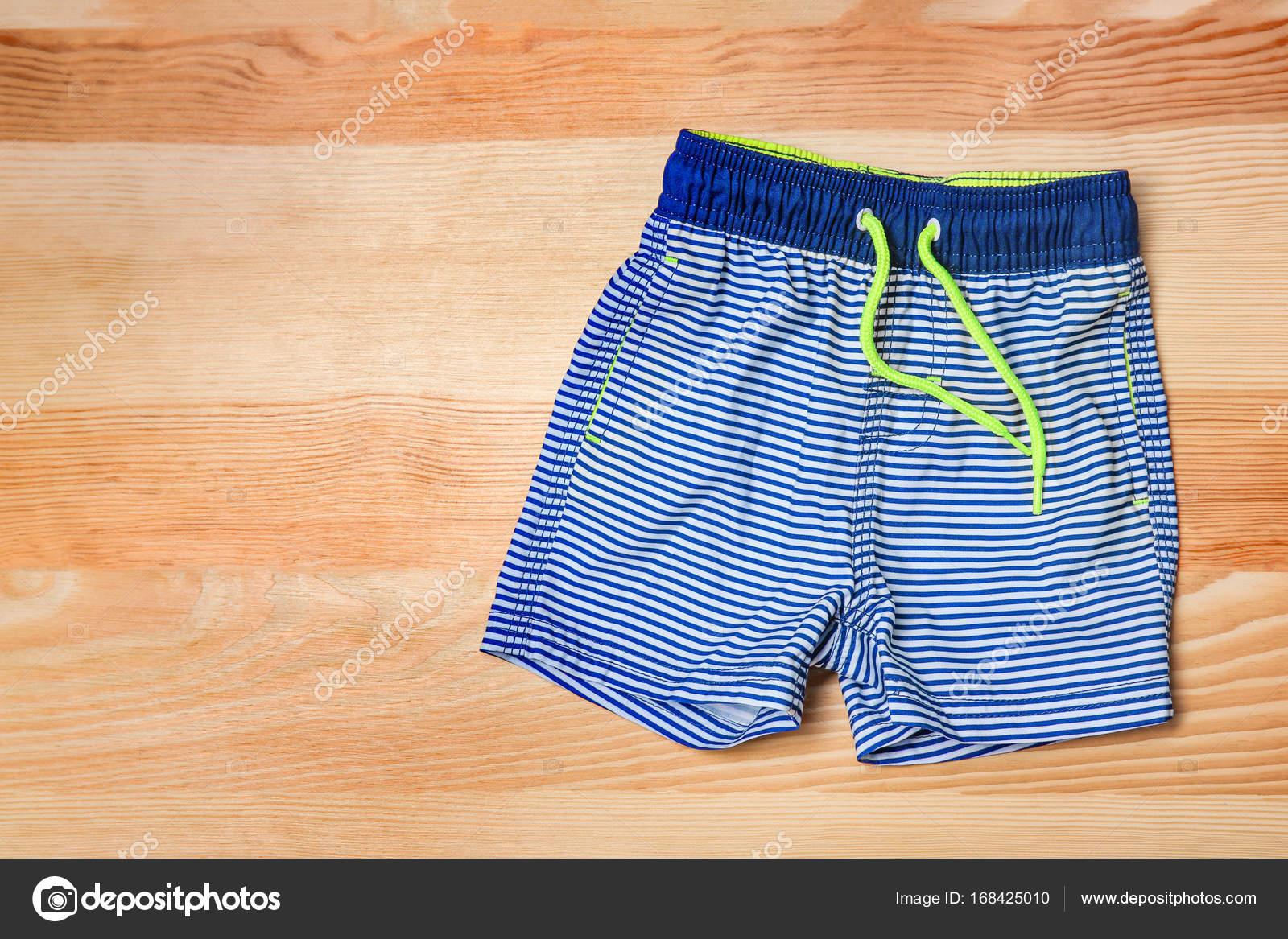 Pantaloncini Da Bagno Ragazzo : Costume da bagno del ragazzo su fondo di legno u foto stock