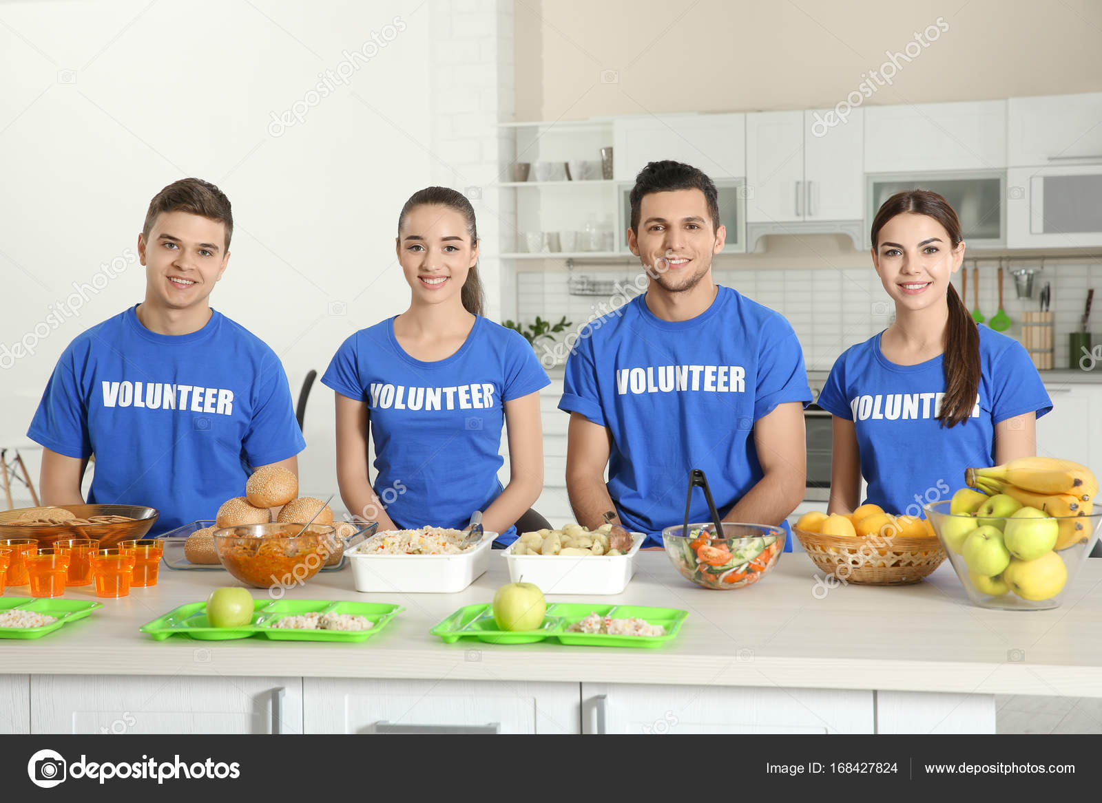 Team Of Teen Volunteers Ready For Serving Food To Homeless People In Kitchen  U2014 Stock Photo
