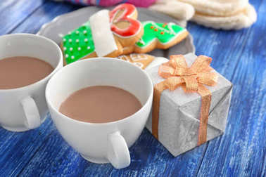 Cups of hot cocoa, gift box and Christmas cookies on color wooden background