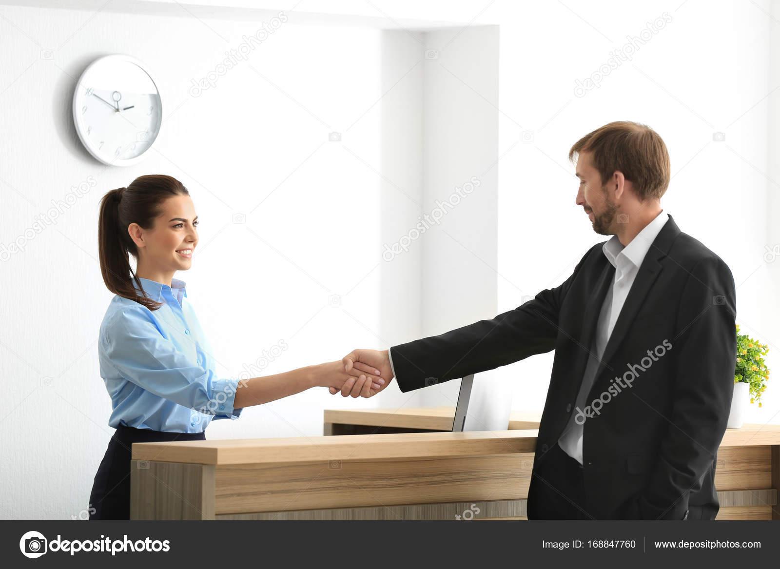 Client de réunion jeune réceptionniste femme au bureau