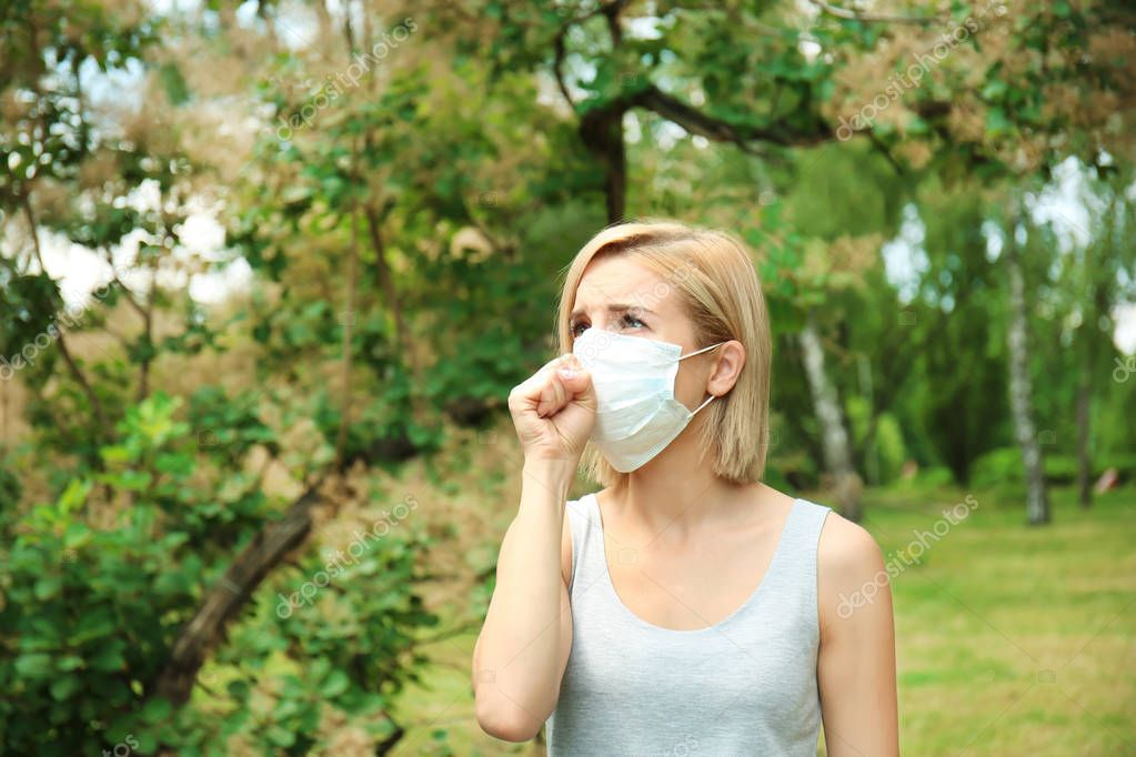 Young woman with allergy outdoors