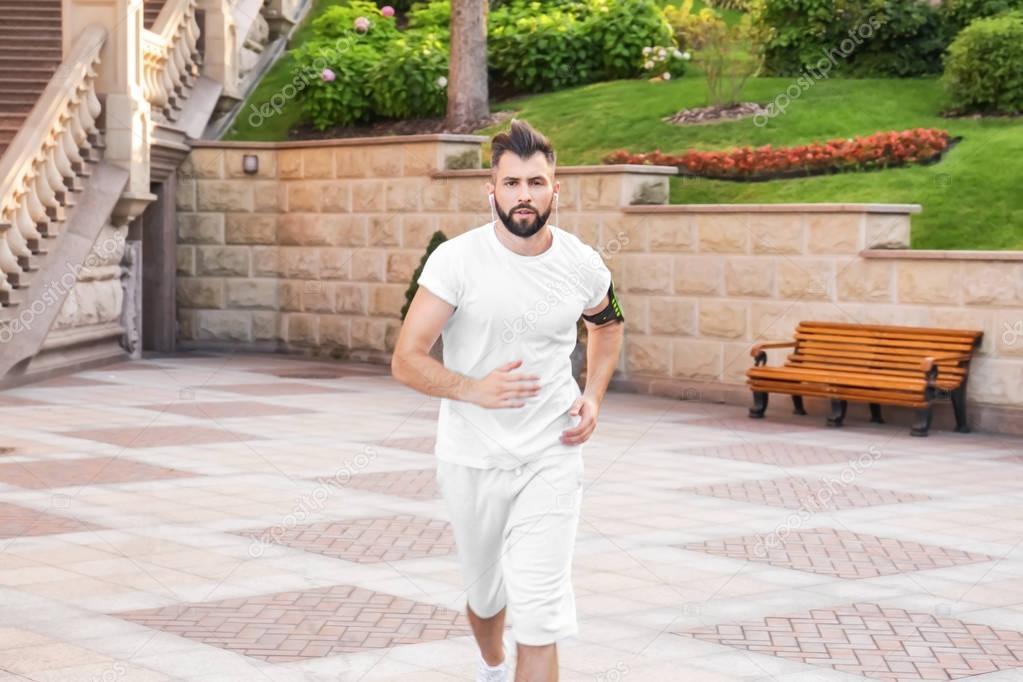 Sporty man running outdoors