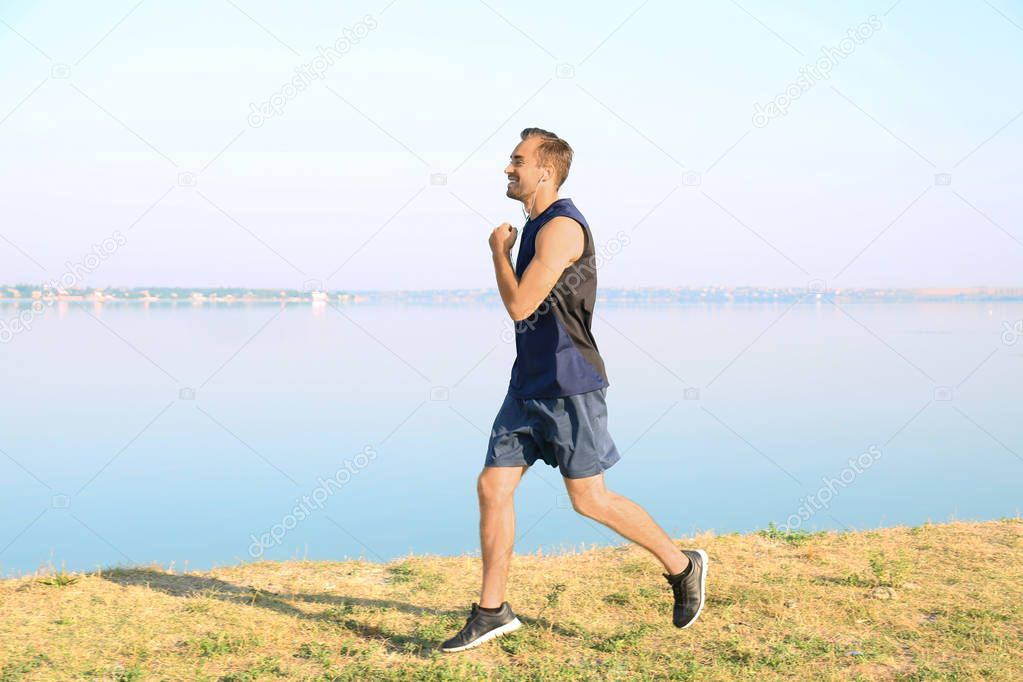 Handsome young man running outdoors