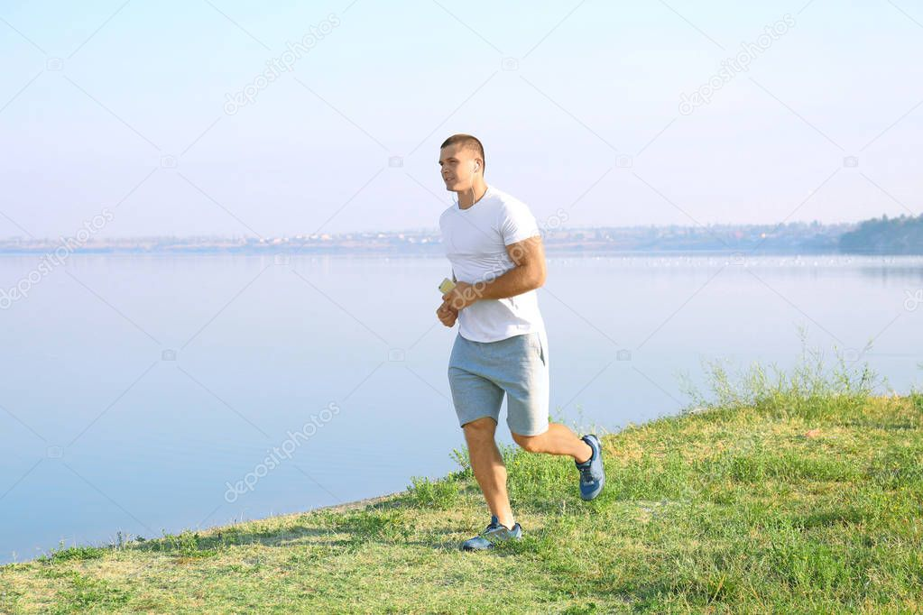 Handsome sporty man running outdoors