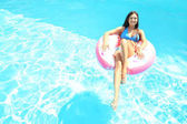 Young beautiful woman sunbathing on   inflatable ring in swimming pool