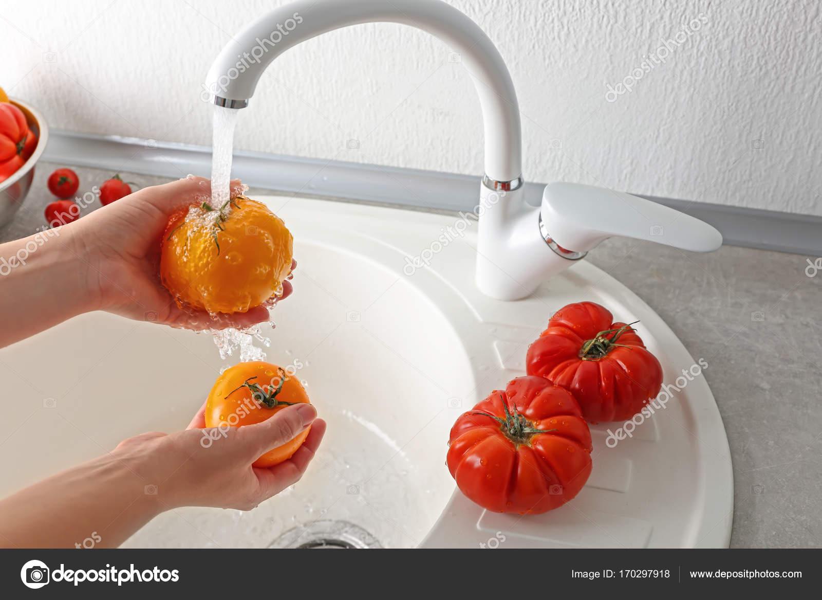 Mujer manos tomate lavado en el fregadero de cocina — Foto de stock ...