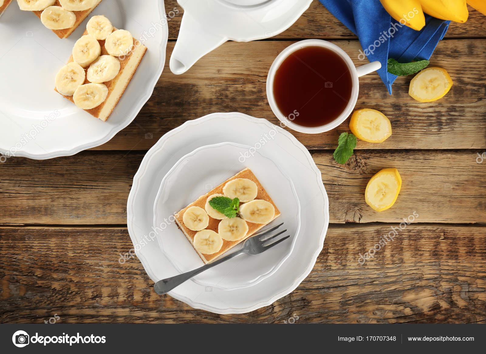 Teller mit leckeren Bananen-Kuchen und Tee auf Holztisch — Stockfoto ...