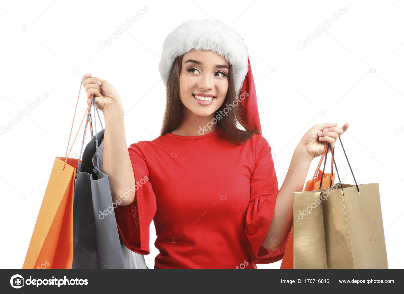 36ae3d25d04ec Young woman in Santa hat holding colorful shopping bags on white  background. Boxing day concept
