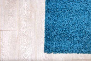 Beautiful blue carpet on wooden floor