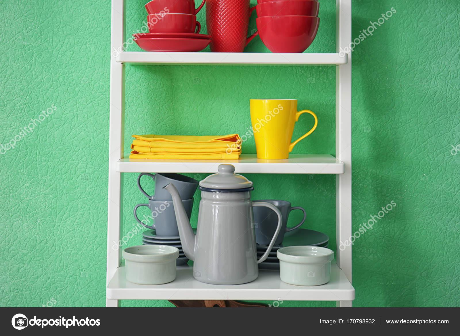Étagère blanche avec la vaisselle en céramique près de mur de ...