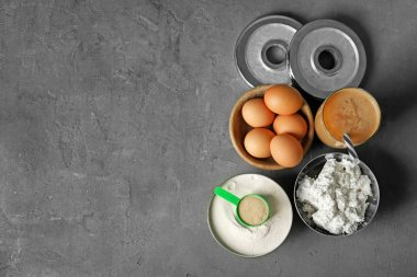 Composition with high protein food, powder and shake on grey background