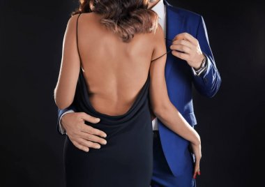 Man in formal suit undressing woman on black background