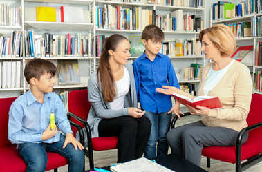 Young mother and children on meeting with teacher at school